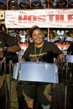 A woman having fun and playing steel drums Stock Photography