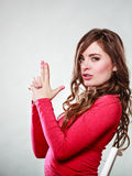Woman having fun pretending hand finger is a gun. Happy woman having fun and fooling around pretending her hand finger is a gun. Joyful girl have nice time Royalty Free Stock Image