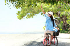 Woman having fun riding bicycle at the beach Stock Images
