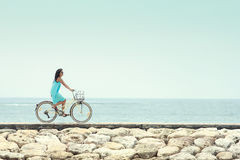 Woman having fun riding bicycle at the beach Stock Photos