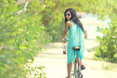 Woman having fun riding bicycle at the beach Stock Image