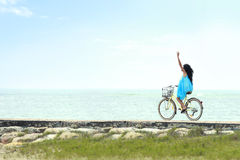 Woman having fun riding bicycle at the beach Royalty Free Stock Photos