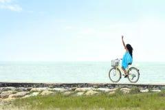 Woman having fun riding bicycle at the beach. Carefree woman having fun and smiling riding bicycle at the beach royalty free stock photos