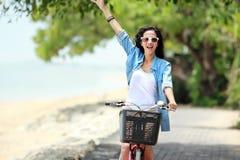 Woman having fun riding bicycle at the beach Stock Image