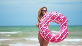 Woman having fun and smile dancing with pink donut. girl in bicini wearing sunglasses on the beach. Beautiful sexy woman. On summer travel vacation stock footage