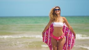 Woman having fun and smile dancing with pink donut. Girl in bikini wearing sunglasses on the beach. Beautiful sexy woman. On summer travel vacation stock footage