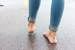 Woman having fun on the street after the rain. Stock Photography