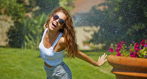Woman having fun in summer garden Stock Images