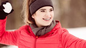 Sporty woman throwing snowball. Woman having fun throwing snowball. Relaxing in winter park wearing fashionable sporty outfit Stock Photo