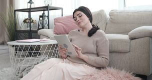 Woman having fun using digital tablet at home. Relaxed young woman having fun using digital tablet at home stock footage