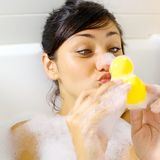 Woman having fun with yellow duck in bathtub Stock Images