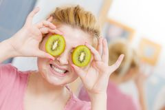 Woman having gel mask on face holding kiwi. Facial skin and body care, vitamins good complexion treatment at home concept. Young woman having gel peel off mask Royalty Free Stock Image