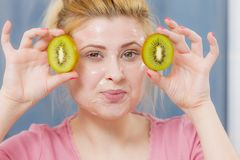 Woman having gel mask on face holding kiwi. Facial skin and body care, vitamins good complexion treatment at home concept. Young woman having gel peel off mask Stock Image