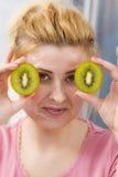 Woman having gel mask on face holding kiwi Stock Image