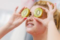 Woman having gel mask on face holding kiwi Royalty Free Stock Image