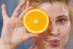 Woman having gel mask on face holding orange Stock Images