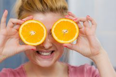Woman having gel mask on face holding orange. Facial skin and body care, vitamins good complexion treatment at home concept. Young woman having gel mask on her Royalty Free Stock Photo