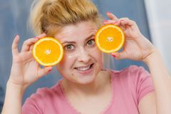 Woman having gel mask on face holding orange. Facial skin and body care, vitamins good complexion treatment at home concept. Young woman having gel mask on her Stock Images