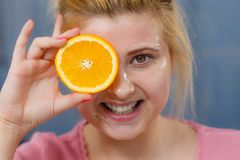 Woman having gel mask on face holding orange. Facial skin and body care, vitamins good complexion treatment at home concept. Young woman having gel mask on her Royalty Free Stock Images