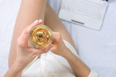 Woman having a glass of wine in bed stock image
