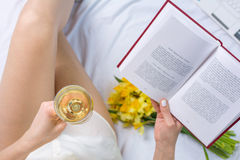 Woman having a glass of wine in bed Stock Photo