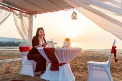Woman having a glass of wine on romantic dinner. Woman having a glass of wine on romantic beach dinner in cabana, sunset, girl, smiling, smile, close, hand stock images