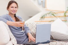 Woman having a glass of wine while using her laptop Royalty Free Stock Image