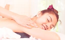 Woman is having a good time white Spa therapist is rubbing her back with scrub. Stock Photo