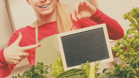 Woman having green vegetables holding board Stock Image