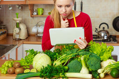 Woman having green vegetables thinking about cooking. Young woman in kitchen having many green vegetables on table, holding tablet thinking about cooking Royalty Free Stock Image