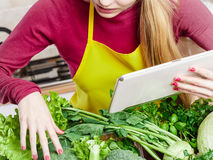 Woman having green vegetables thinking about cooking. Young woman in kitchen having many green vegetables on table, holding tablet thinking about cooking stock image