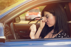 Woman having headache taking off glasses after driving car in traffic jam Stock Image