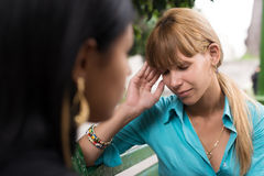 Woman having headache while talking with friend Stock Photos