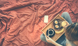 Woman is having a healthy breakfast in bed. Royalty Free Stock Photos