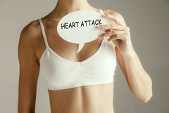 Woman having a heart attack. Woman health. Female model holding card with words HEART ATTACK near breast. Medical problem and solution stock photos