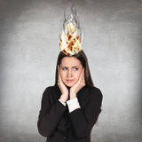 Woman having her brain on fire because of stress. On a gray background Stock Photo