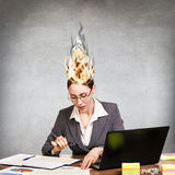 Woman having her brain on fire because of stress. On a gray background Royalty Free Stock Photography
