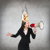 Woman having her brain on fire because of stress. On a gray background Royalty Free Stock Photos