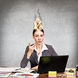 Woman having her brain on fire because of stress. On a gray background Royalty Free Stock Photo