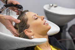 Woman having her head washed by hairdresser Stock Images