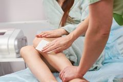 Woman having her legs waxed. stock photos