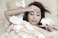 Woman having high fever. Woman is having high fever and resting on her bed Royalty Free Stock Photography