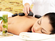 Woman having hot stone massage of back in spa salon. Woman having hot stone spa massage of back in beauty salon stock images
