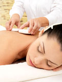 Woman having hot stone massage of body in spa salon Stock Image