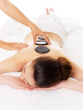 Woman having hot stone massage in spa salon. Royalty Free Stock Photos
