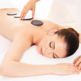 Woman having hot stone massage in spa salon. Adult  woman having hot stone massage in spa salon. Beauty treatment concept Royalty Free Stock Photo