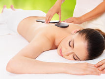 Woman having hot stone massage in spa salon. Royalty Free Stock Images