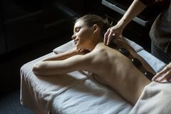 Woman having a hot stone massage therapy Royalty Free Stock Photos