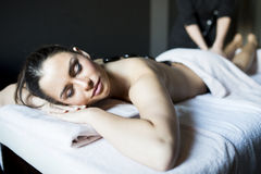 Woman having a hot stone massage therapy Stock Images