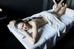 Woman having a hot stone massage therapy Stock Photos